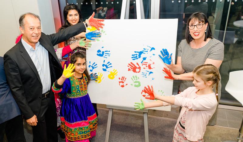 Staffelei mit Bild, auf dem farbige Handabdrücke zu sehen sind, Kinder und Erwachsene (Naim Ziayee, Sarina Ziayee, Karin-Brigitte Göbel).